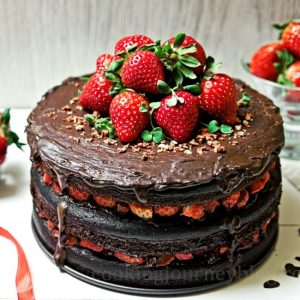 Vegan chocolate cake, decorated with fresh and dry strawberries