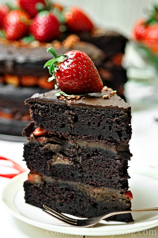 Vegan chocolate cake, decorated with strawberry, served on a plate