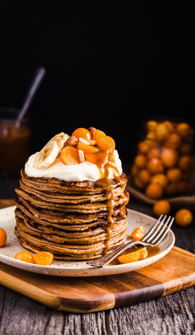 Protein pancake stack, served on a plate with cream and fruits on top