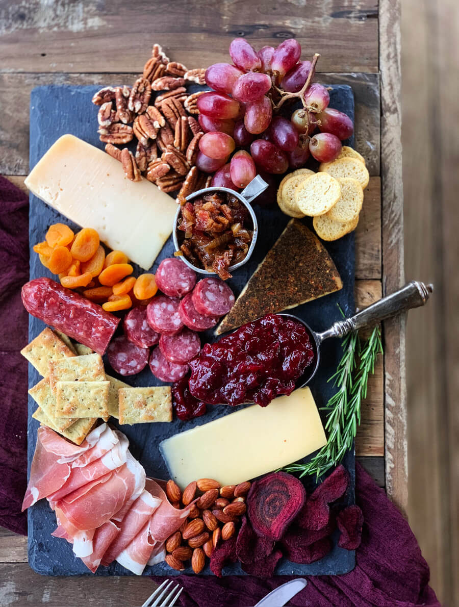 Board filled with different types of cheese, bacon, jam, nuts and grapes
