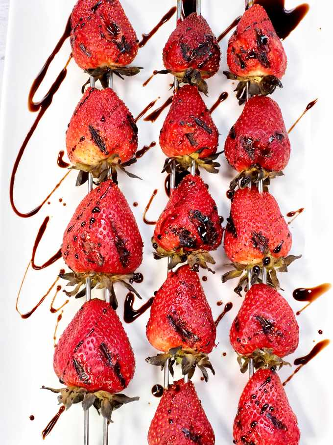 Grilled strawberries with balsamic, served on a white plate