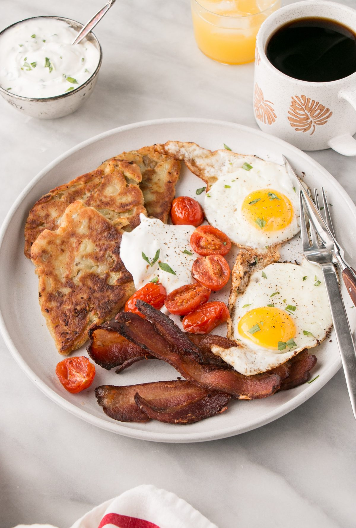 Potato scones, served with eggs, bacon and tomatoes on the white plate