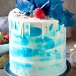Vanilla Cake Recipe (Birthday Cake Recipe). Sky blue cake, decorated with white chocolate glaze, inserted edible blue glass, strawberry and blueberries.