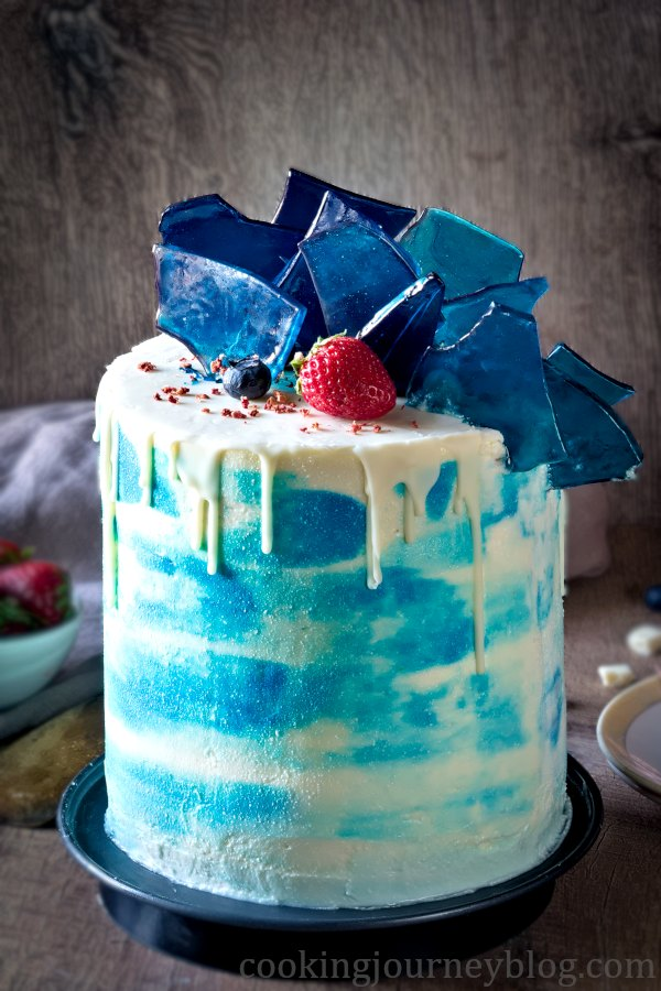 Blue and white vanilla cake for men, decorated with edible blue glass and berries
