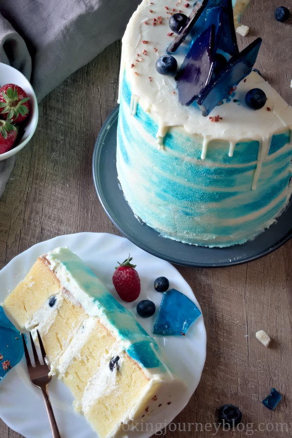 A slice of vanilla cake on a plate and a cake, view from top.