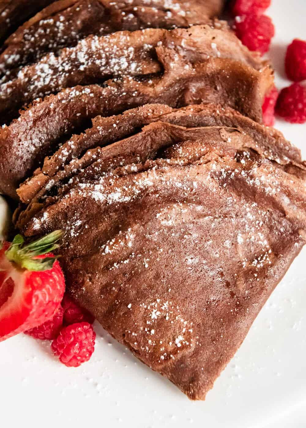 Chocolate crepes, served on a plate with red berrries