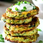 Easy Zucchini Fritters, served on a white plate with Greek yogurt and scallions