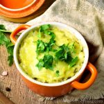 Cheesy hashbrown casserole recipe. Served in an orange pot with parsley
