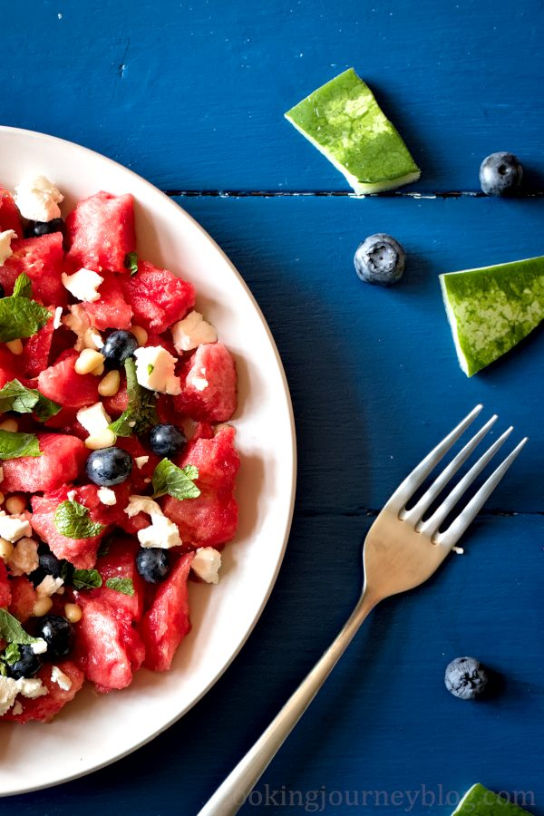 Watermelon feta salad on a blue table, view from top