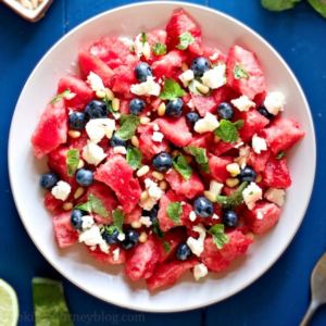 Watermelon Feta Salad, served on a plate with fork, lime, mint and pine nuts on the blue table