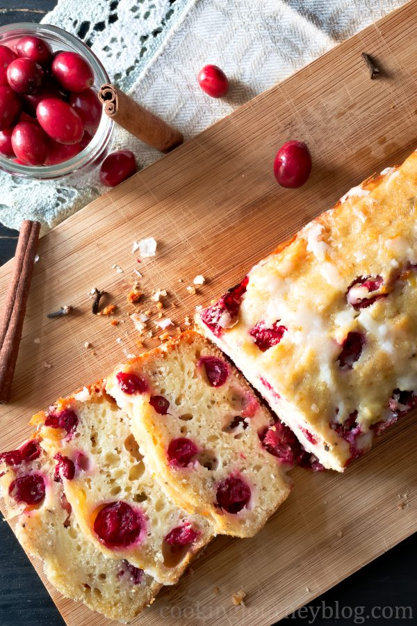 Cranberry Orange Bread served on the board with fresh cranberries and cinnamon