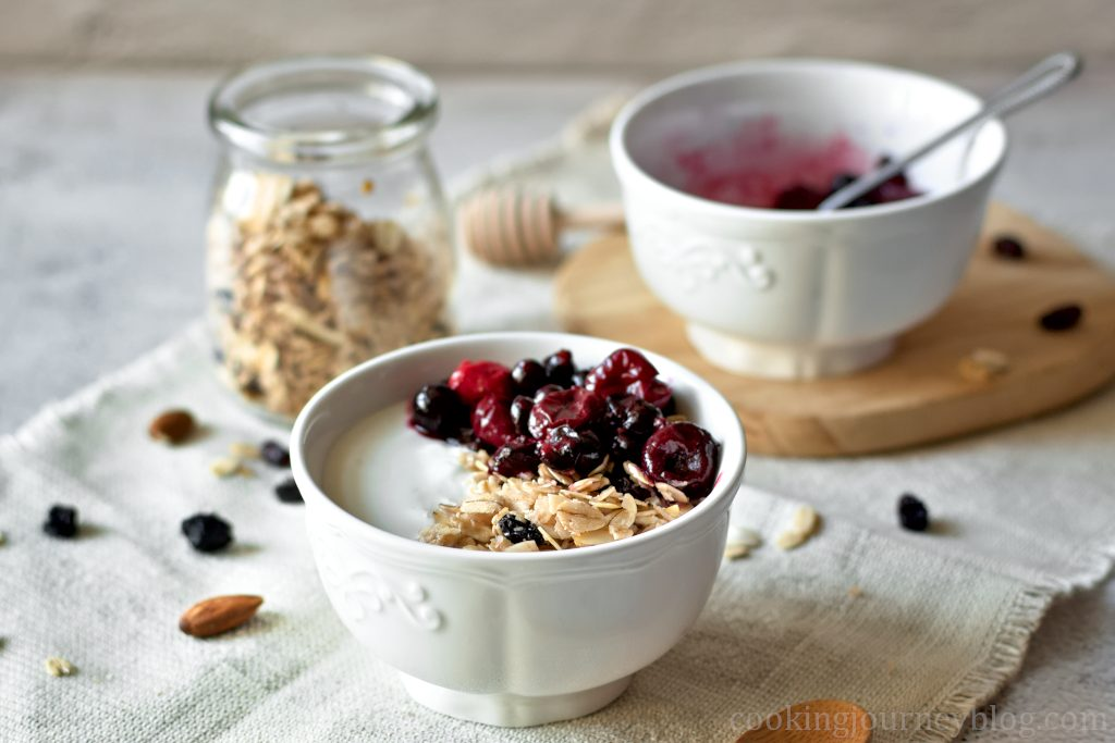 Homemade Granola served with yogurt and berries in a white bowl