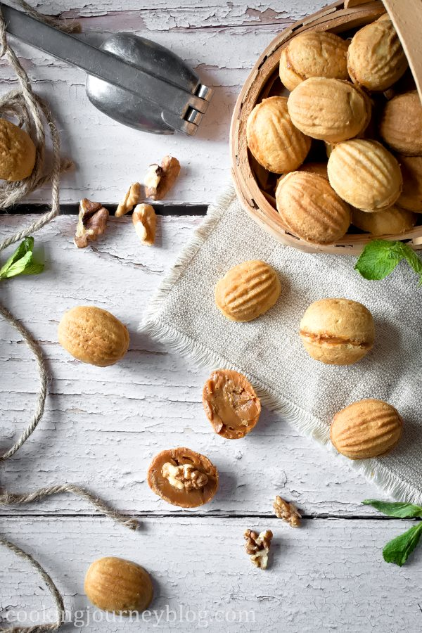 Walnut shaped cookies with condensed milk on a table