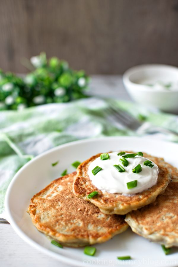 Irish boxty pancakes served on a plate with cream and scallions.