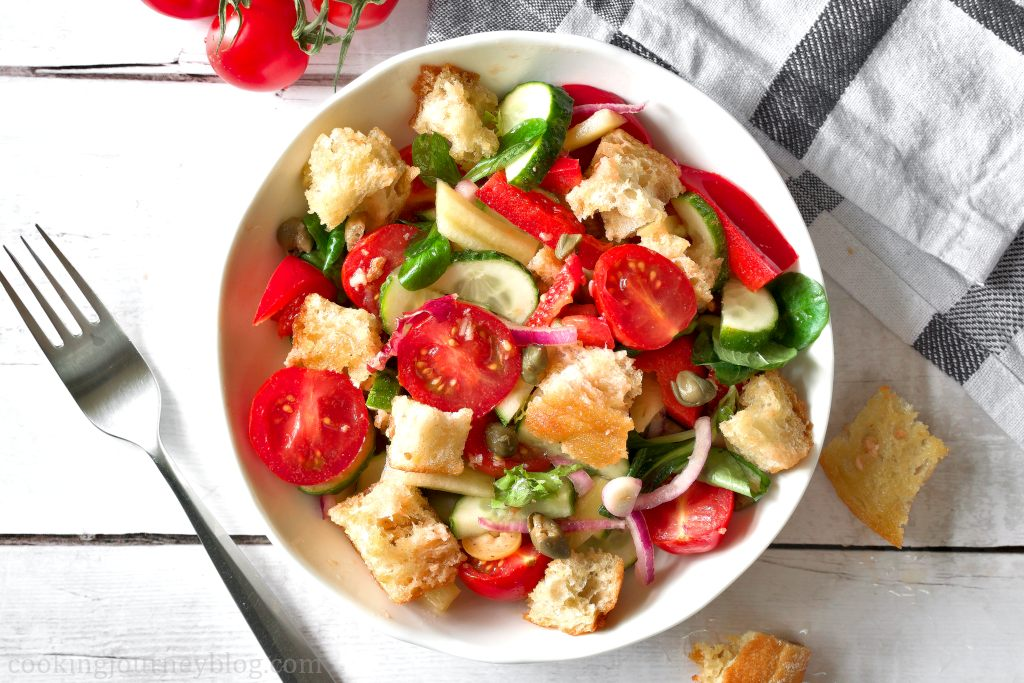 Panzanella salad in a white bowl, served with a fork and a napkin