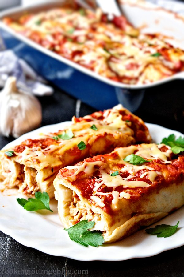 Chicken enchiladas on a plate and enchilada bake in the background