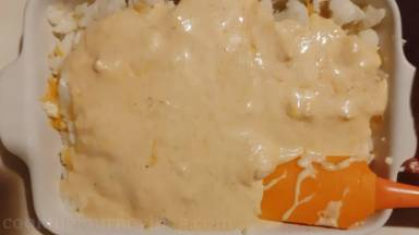 Add leftover cauliflower floret and cover with cheese sauce, spreading with spatula.