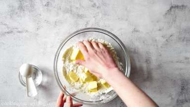 Add butter to flour and mix with your hands.