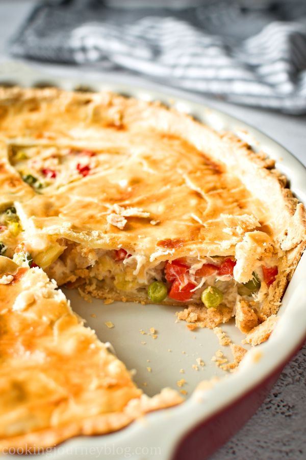 Chicken pot pie without a slice in a red pie pan