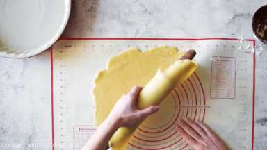 Using the rolling pin, carefully roll the crust on it and transfer to the pie pan.