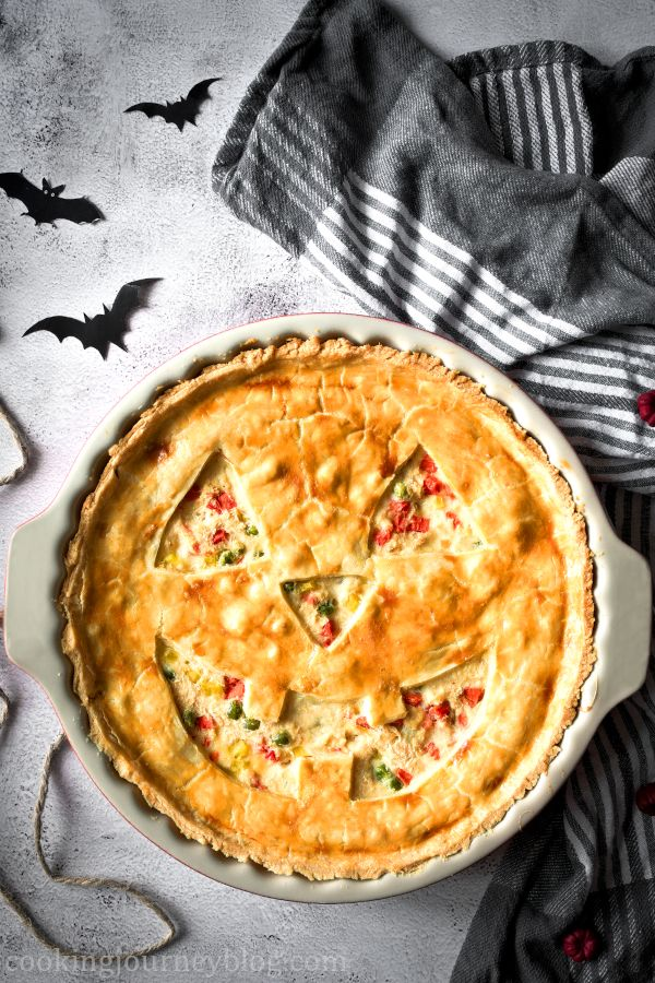 Jack-O'-Lantern Chicken Pot Pie on a gray table with kitchen towel