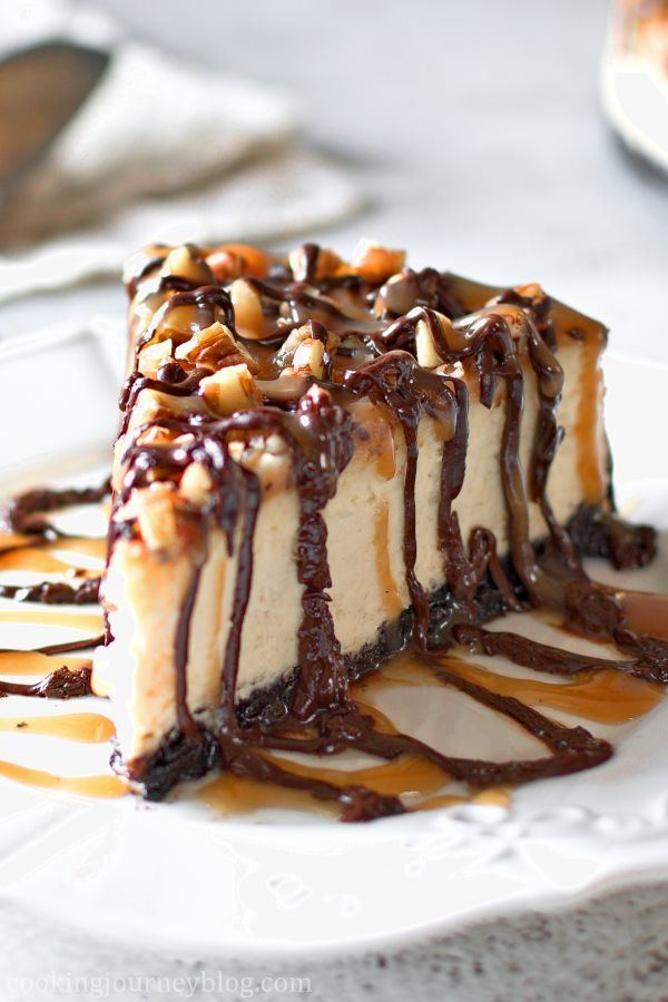 A slice of Luscious Turtle Cheesecake on a white plate, with caramel and chocolate sauce and pecans