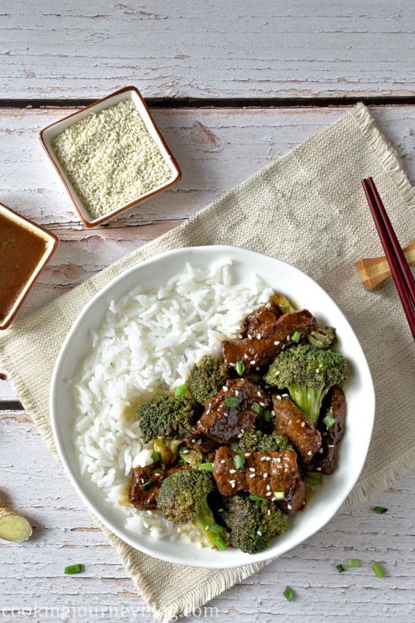 A bowl with rice, served with beef and broccoli on top, chopsticks and extra soy sauce on the side