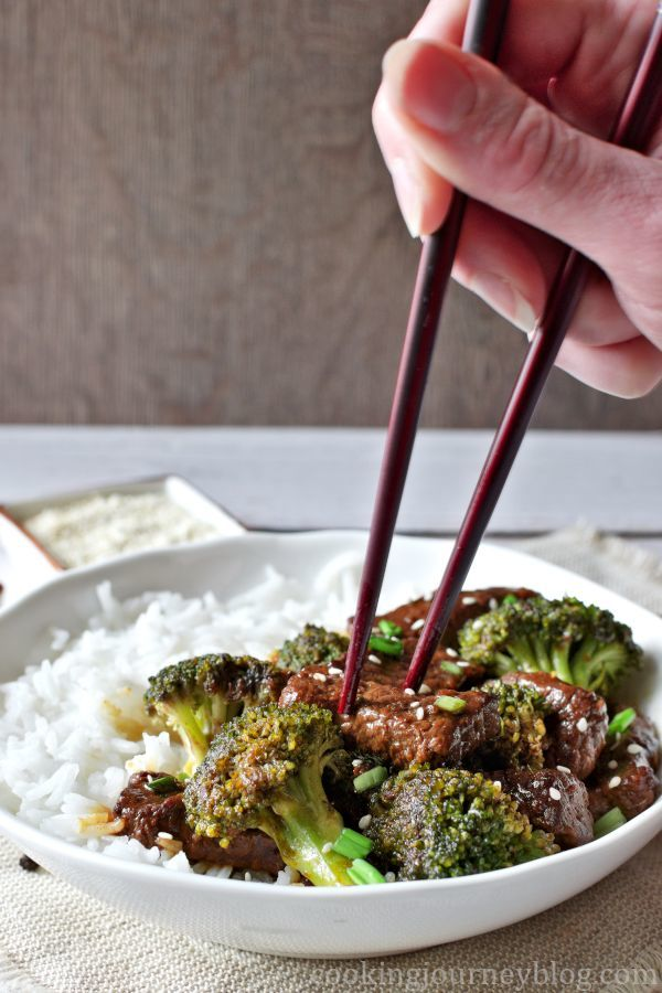 Beef and Broccoli Stir Fry in a white bowl, with hand holding Chinese chopsticks