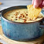 Chile con Queso dip in a blue bowl with tortilla chip.