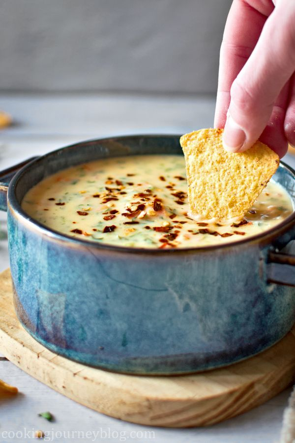 Dipping tortilla chips in chile con queso in a blue bowl