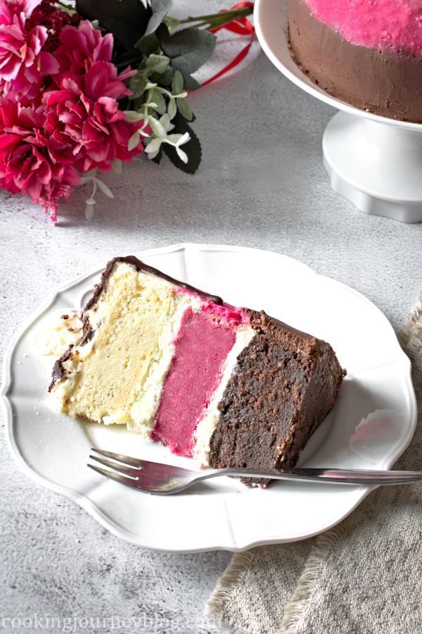 A piece of Neapolitan Cake, served on a white plate with fork