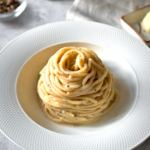 Spaghetti Cacio e Pepe served on a white plate with whole peppercorns, cheese, pestle and mortar in background