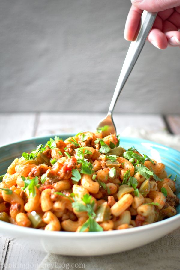 Eating easy American Chop Suey with a fork from the blue plate