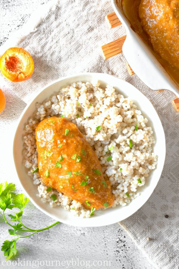 Baked apricot chicken served with barley in a white bowl on the gray table with fresh apricots