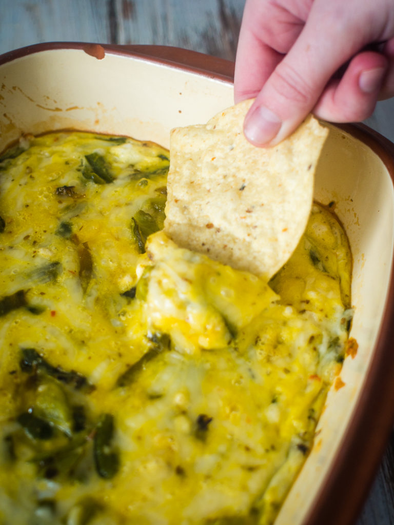 Dipping chips in Chile Relleno casserole