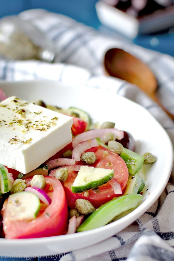 Horiatiki Greek salad served in a white bowl with wooden tablespoon