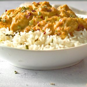 Peanut butter chicken served with a bowl of rice, with scallions and chili flakes on top.