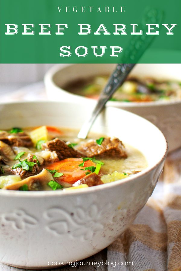 Vegetable beef barley soup in a white bowl with spoon